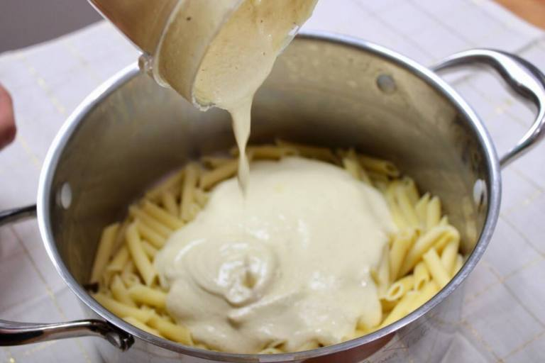 pouring cashew alfredo over pasta