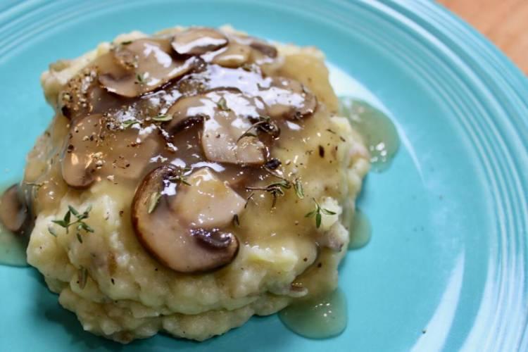 Garnished mashed potatoes with mushroom gravy