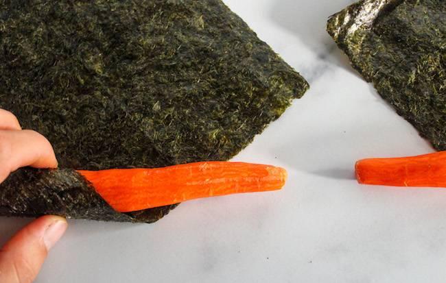 Rolling a peeled carrot in a nori sheet